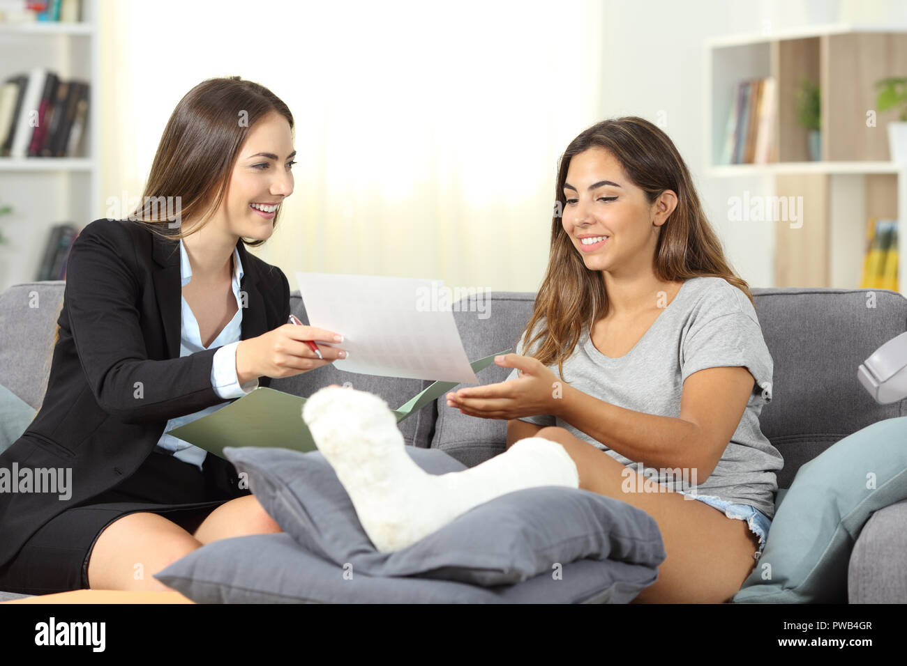 Happy insurance agent giving notification to a disabled girl sitting on a couch at home - Stock Image