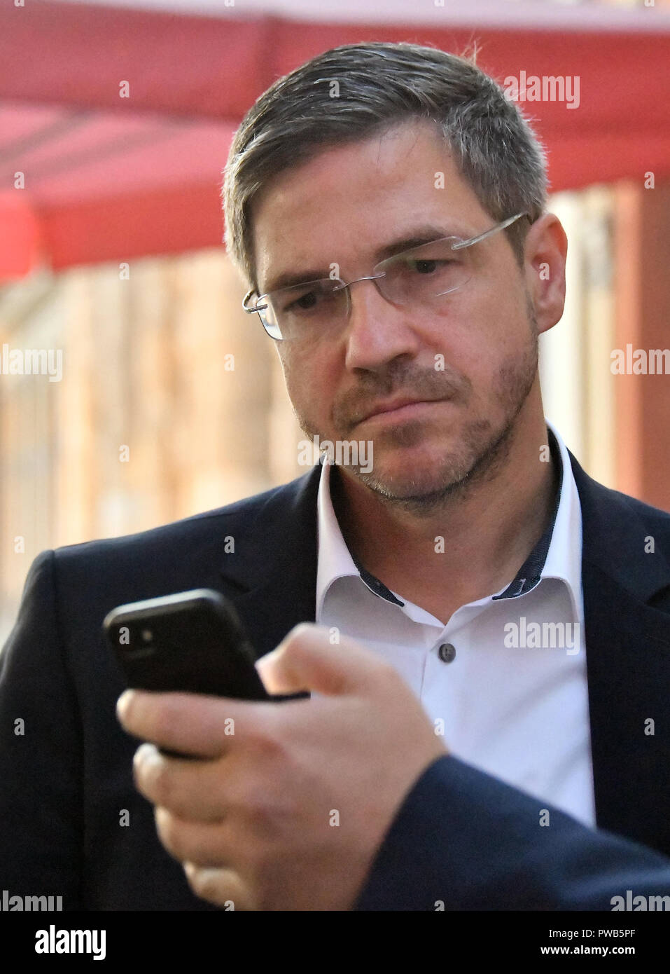 Potsdam, Brandenburg. 14th Oct, 2018. 14 October 2018, Germany, Potsdam: Mayor candidate Mike Schubert (SPD) looks at a mobile phone with the first results of the vote count. Credit: Bernd Settnik/dpa-Zen tralbild/dpa/Alamy Live News - Stock Image