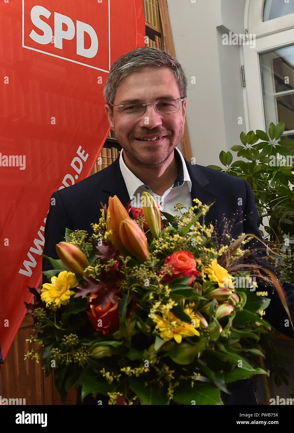 Potsdam, Brandenburg. 14th Oct, 2018. 14 October 2018, Germany, Potsdam: Mike Schubert (SPD) stands at the election party with a bouquet of flowers. He was elected the new Lord Mayor with 55.3 percent of the votes. Credit: Bernd Settnik/dpa-Zen tralbild/dpa/Alamy Live News - Stock Image