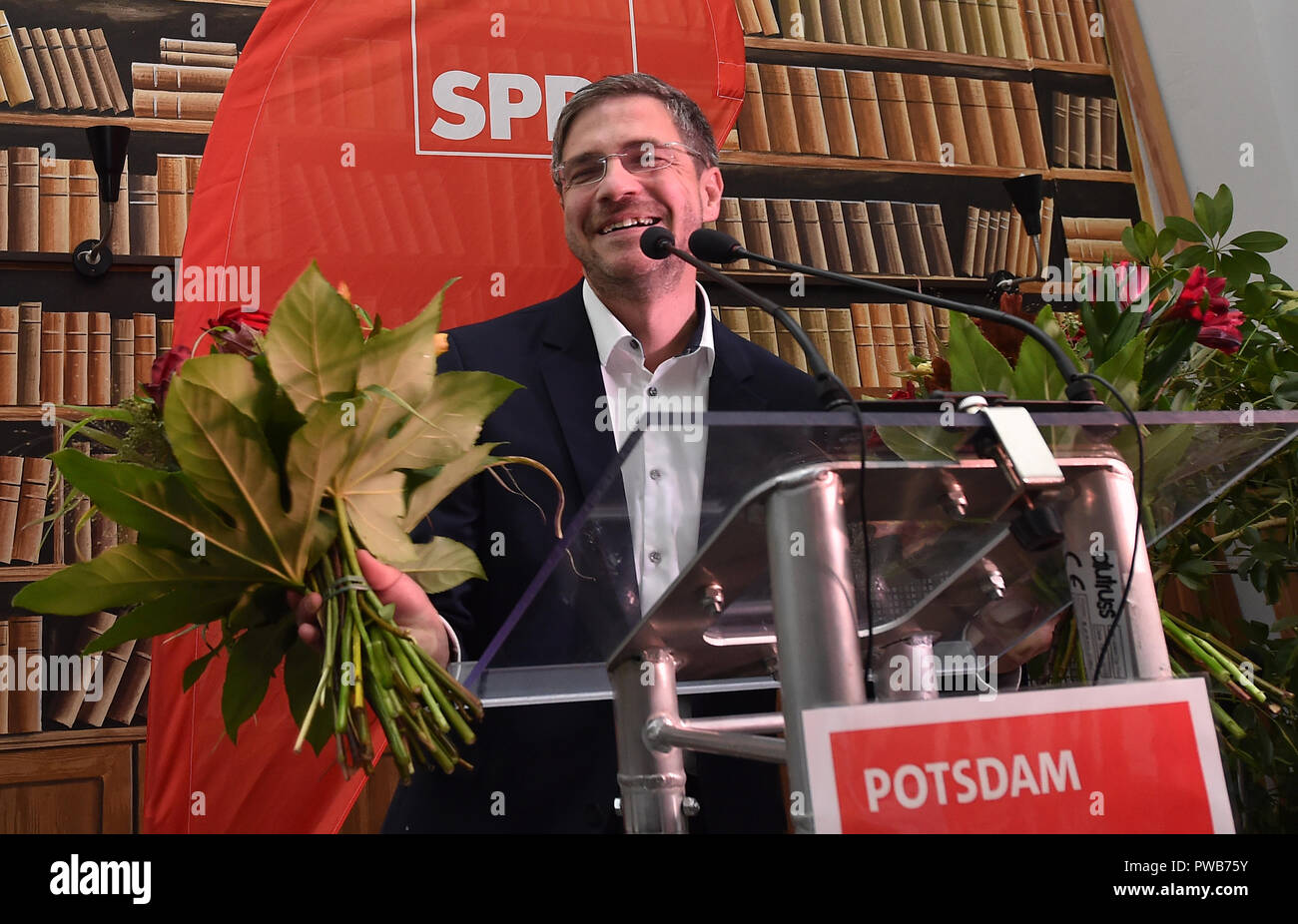 Potsdam, Brandenburg. 14th Oct, 2018. 14 October 2018, Germany, Potsdam: Mike Schubert (SPD) is at the election party with two bouquets of flowers. He was elected the new Lord Mayor with 55.3 percent of the votes. Credit: Bernd Settnik/dpa-Zen tralbild/dpa/Alamy Live News - Stock Image