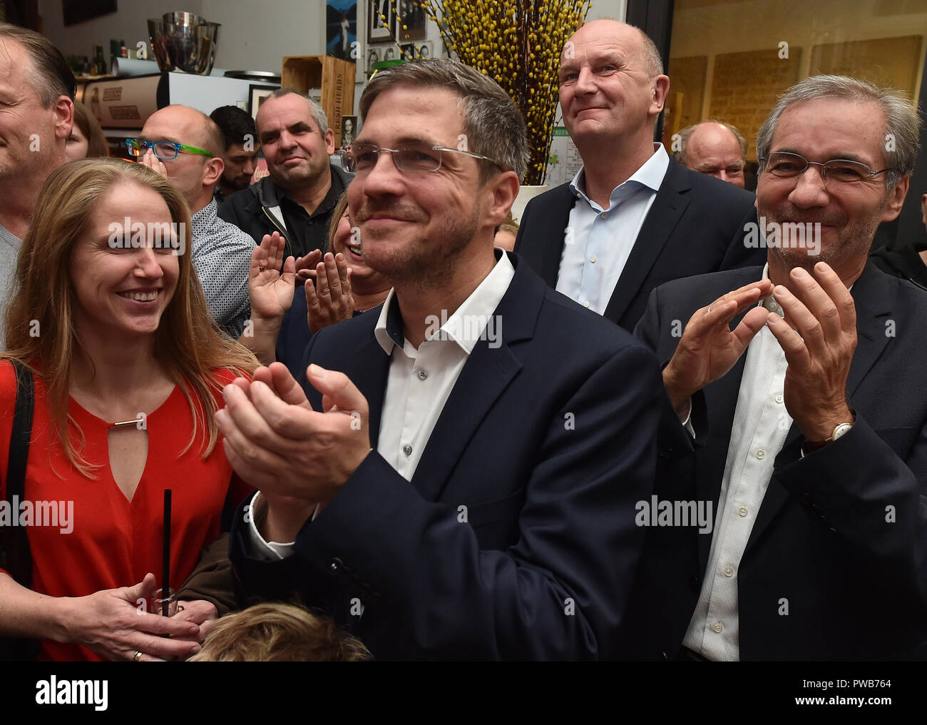 Potsdam, Brandenburg. 14th Oct, 2018. 14 October 2018, Germany, Potsdam: Mike Schubert (SPD) is at the election party between his wife Simoned, Dietmar Woidke (SPD, 2-R), Minister President of Brandenburg, and Matthias Platzeck (SPD, R), former Minister President of Brandenburg. Schubert was elected new Lord Mayor with 55.3 percent of the votes. Credit: Bernd Settnik/dpa-Zen tralbild/dpa/Alamy Live News - Stock Image