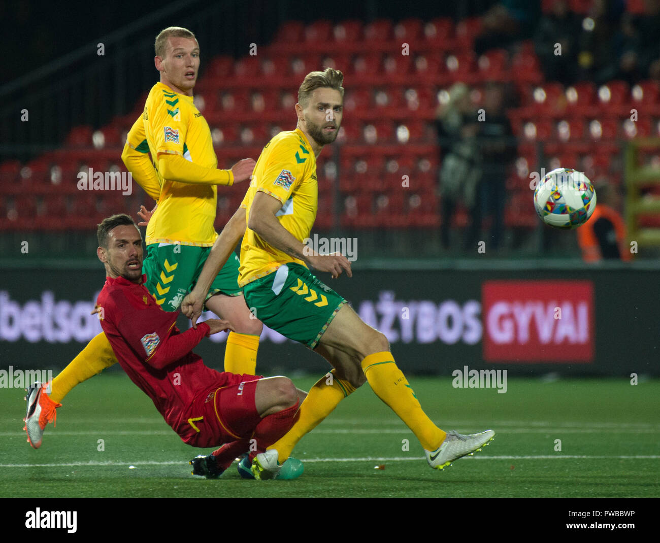 Vilnius, Lithuania. 14th Oct, 2018. Marko Vesovic (Bottom) of Montenegro vies with Arturas Zulpa (R) of Lithuania during the UEFA Nations League C match at LFF Stadium in Vilnius, Lithuania, on Oct. 14, 2018. Montenegro won 4-1. Credit: Alfredas Pliadis/Xinhua/Alamy Live News - Stock Image