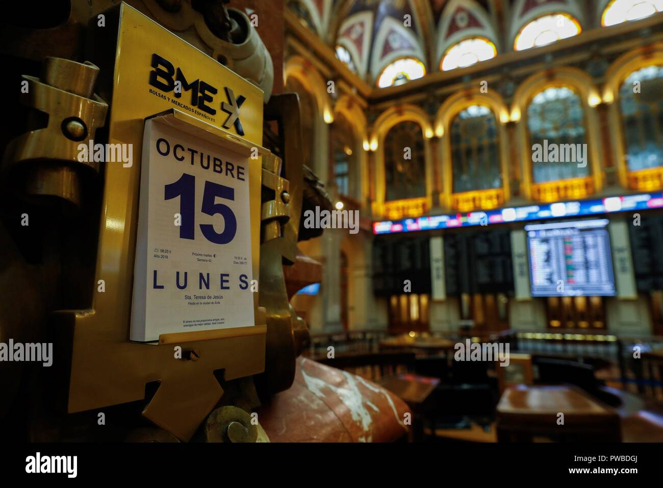 Madrid, Spain. 15th Oct, 2018. A calendar shows the date as an information panel (background) shows the evolution of Spanish index IBEX 35 at the stock market in Madrid, Spain, 15 October 2018. The IBEX 35 dropped a 0.06 per cent at the start of the trading day down to 8,896 points. Credit: Emilio Naranjo/EFE/Alamy Live News - Stock Image