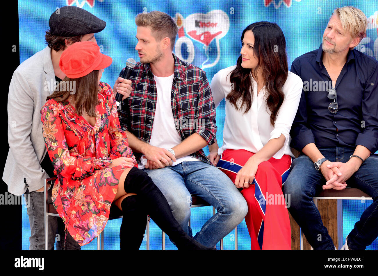 Soltau, Lower Saxony. 14th Oct, 2018. Singer Sarah Lombardi (l-r), presenter Tommy Scheel, actor Jörn Schlönvoigt, actress Bettina Zimmermann and actor Kai Wiesinger sit on a stage in Heide-Park during an event of the company Kinder Schokolade. The Kinder brand celebrates its 50th anniversary with a family celebration in the park. Credit: Hauke-Christian Dittrich/dpa/Alamy Live News Stock Photo