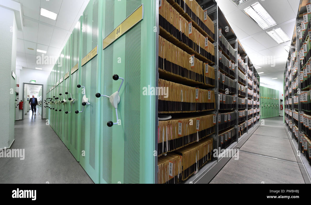 15 October 2018, Thuringia, Jena: An employee walks along the shelves in the trademark archive of the Jena office of the German Patent and Trademark Office. The East German branch of the Patent Office in Munich has been in existence for 20 years. The settlement was decided by the Federalism Commission in 1992. Since then, the employees have been responsible for design protection and, together with Munich, for trademark protection. The branch currently employs a total of 229 civil servants and employees. Photo: Martin Schutt/dpa-Zentralbild/dpa Stock Photo