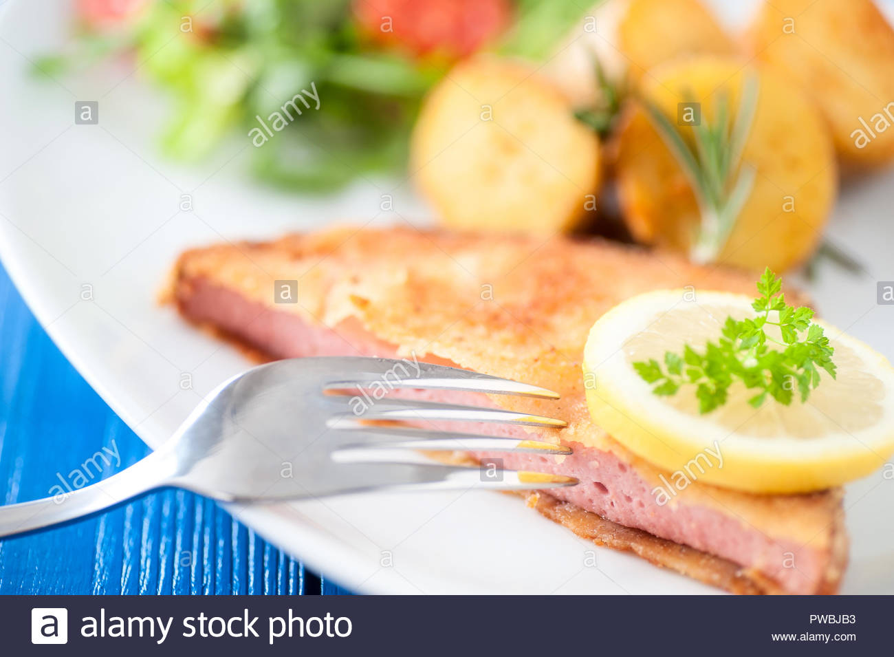 breaded leberkäse with roasted potatoes and sald on plate typical