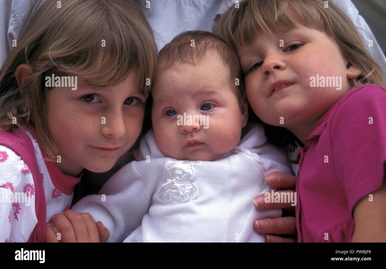 Three siblings, baby toddler and young girl - Stock Image