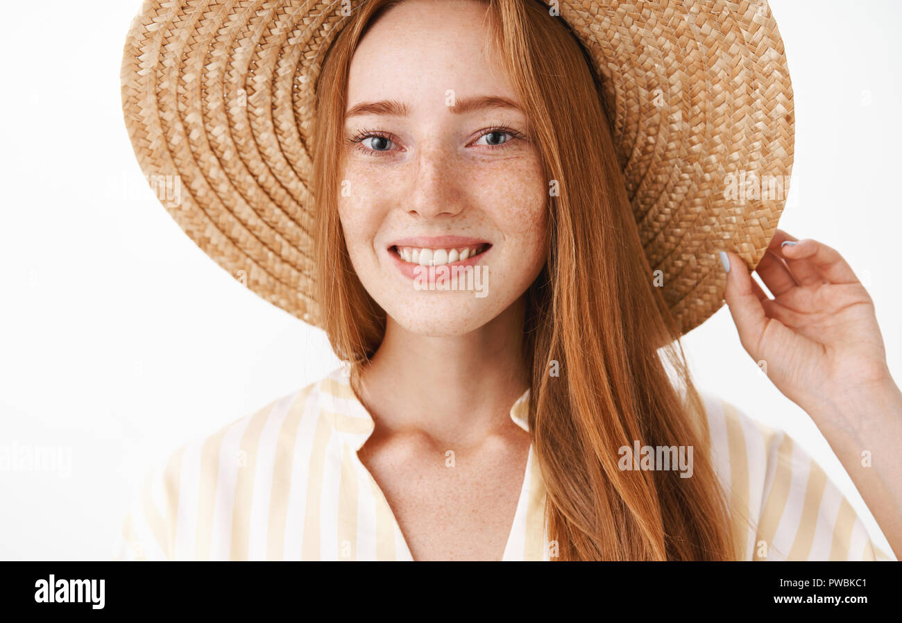 Headshot of happy charming redhead girl enjoying vacation smiling broadly at camera holding straw hat on head and gazing at camera with friendly delighted expression over white background Stock Photo