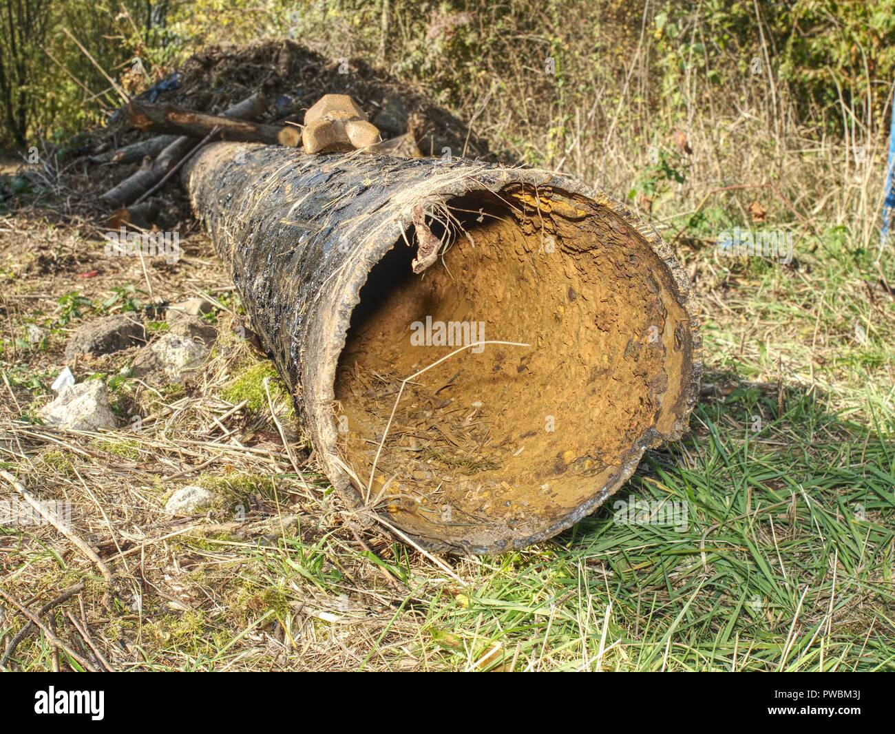 Long metal pipe laying on ground. Broken rusty steel tube. Open trench with water pipe and heap of ground near. - Stock Image