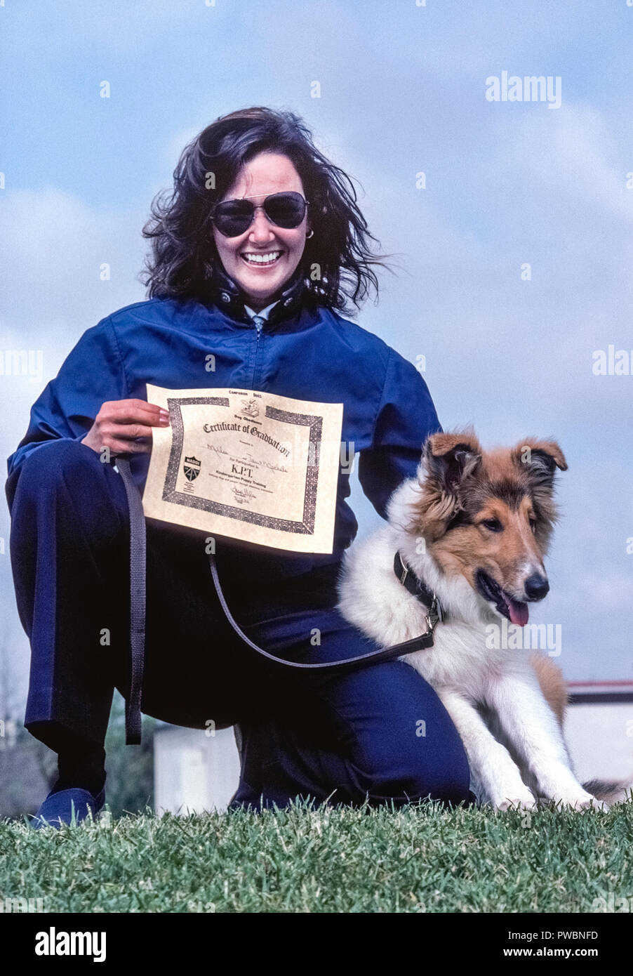 This proud female owner of a young tricolor collie displays the Certificate of Graduation her dog received after completing Kindergarten Puppy Training (K.P.T.), a pet behavioral program that was offered in the 1970s by the city recreation department of Laguna Beach, California, USA. - Stock Image