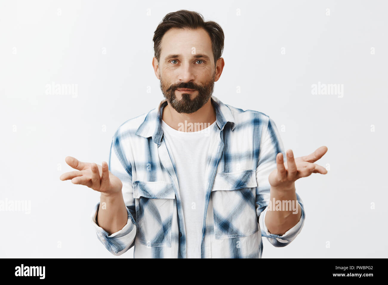 Who cares, realxed and chill. Portrait of calm and indifferent attractive male model with beard, raising palms in questioned gesture and gazing with careless expression at camera, without any worries - Stock Image