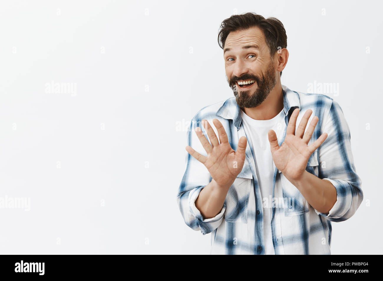 Thanks I am fine. Nervous polite good-looking mature male rejecting offer from stranger with friendly expression, saying no, raising palms and waving them in stop or not gesture, giving refusal - Stock Image