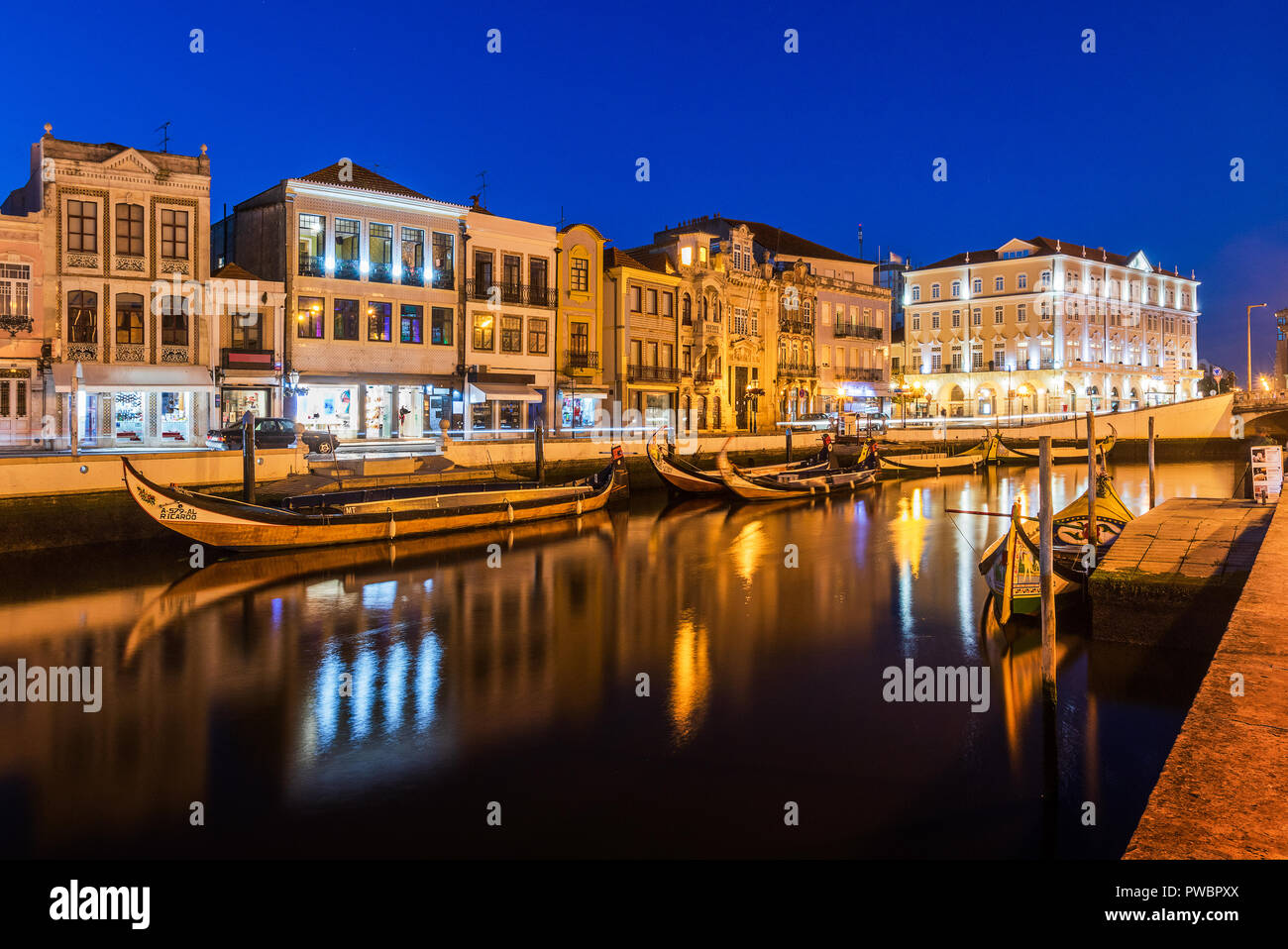 Central canal in Aveiro, with several moliceiros anchored and houses Art Noveau in the background at nightfall. Center of the city of Aveiro, in Portu - Stock Image