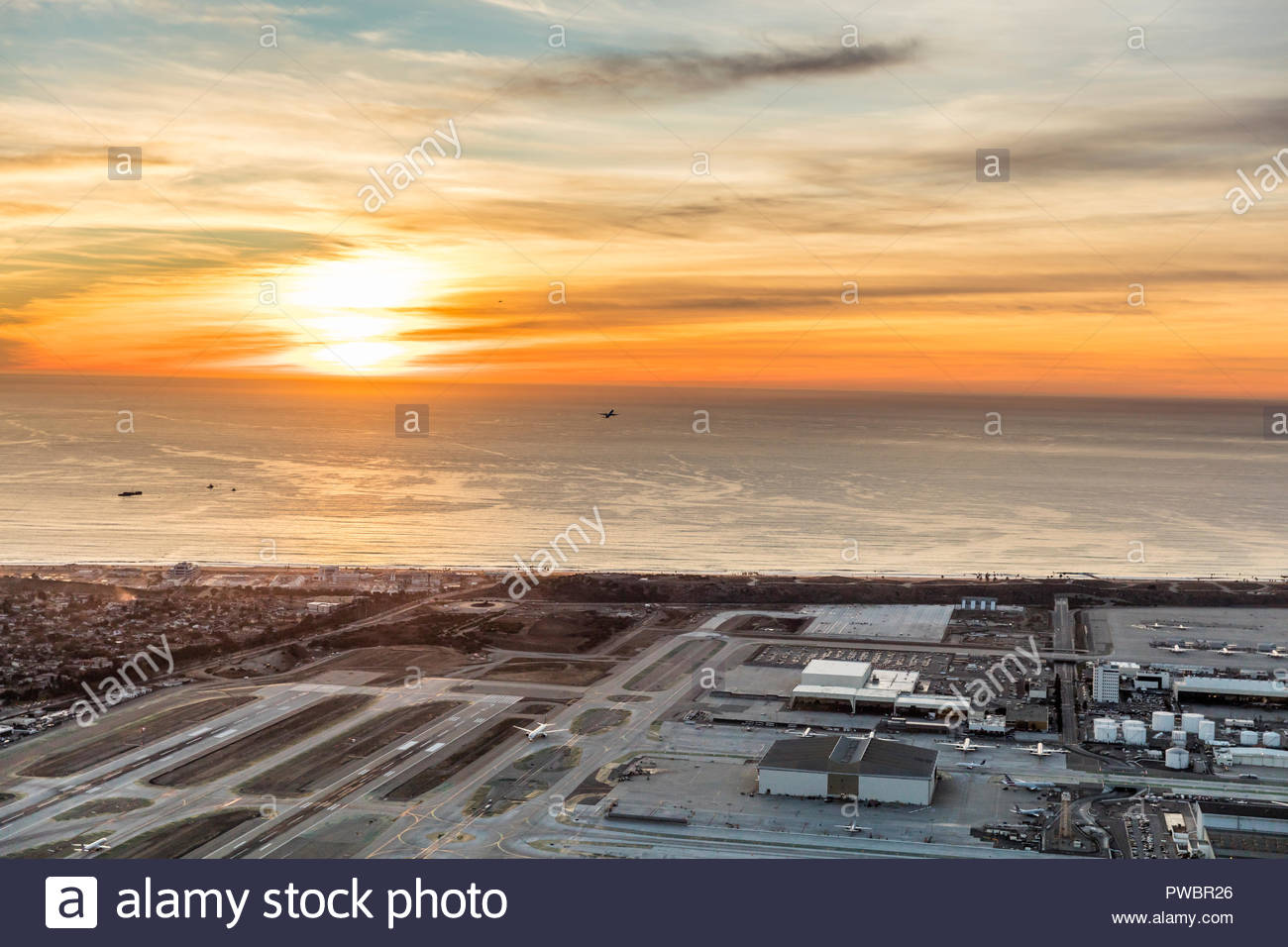 Airplanes taking off from Los Angeles International Airport at sunset. - Stock Image
