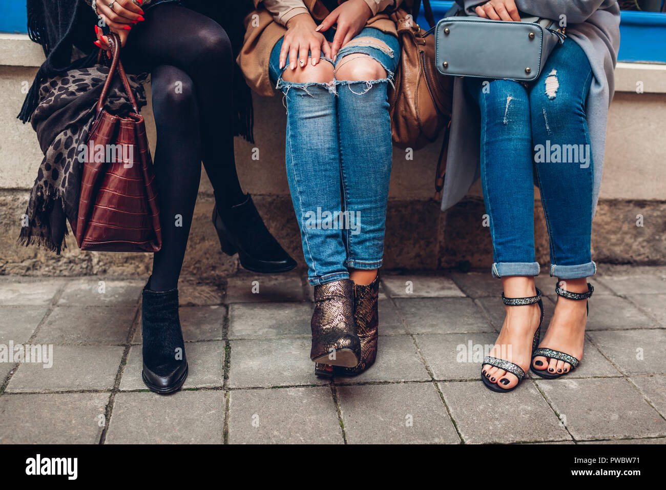 Three women wearing stylish shoes, clothing and accessories