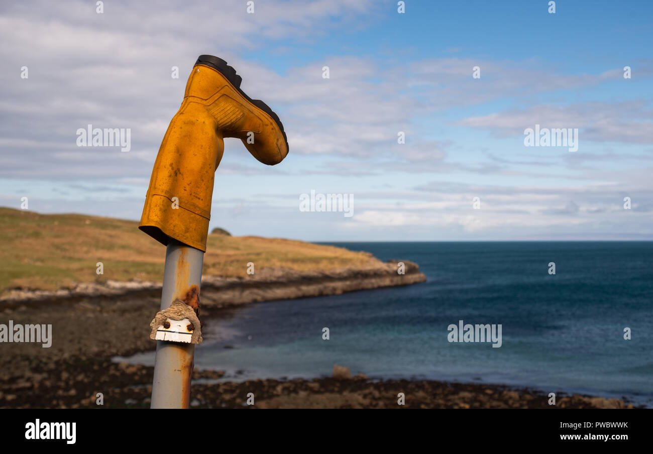 A Yellow rubber boot put on a metal post pillar, Isle of Skye, Scotland, Uk Stock Photo