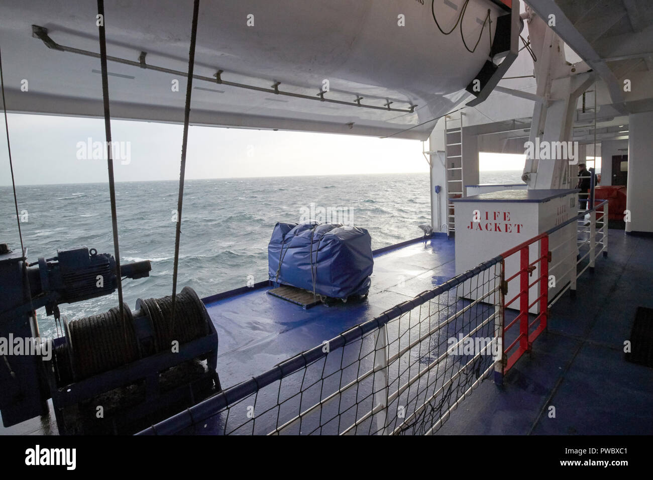 life jackets and lifeboat at muster station on stena line ferry making rough irish sea crossing during storm - Stock Image