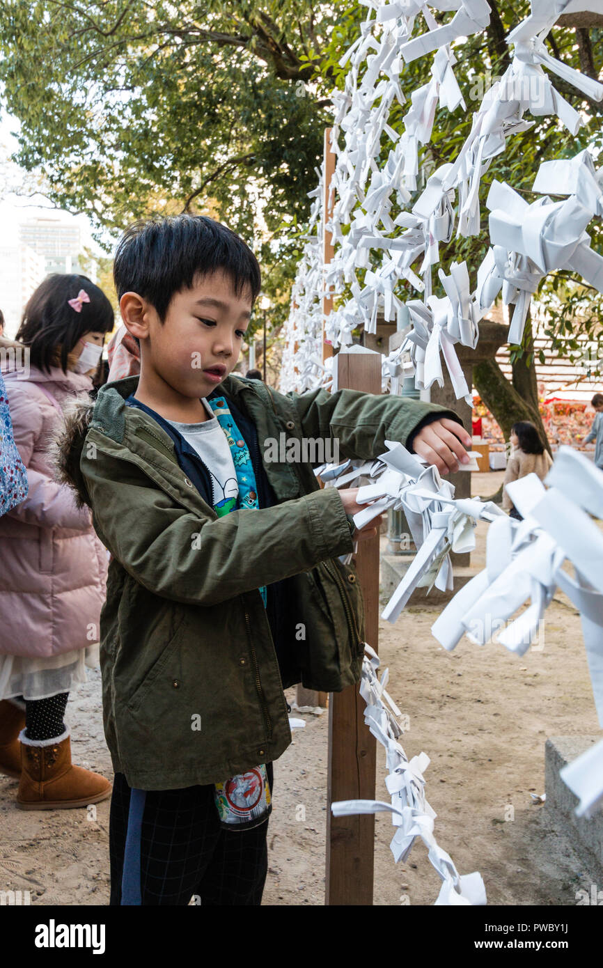 Japanese new year, shogatsu. Young child, boy, tying bad fortune paper slip, Omikuji to framework to leave bad luck behind at the Nishinomiya shrine. - Stock Image