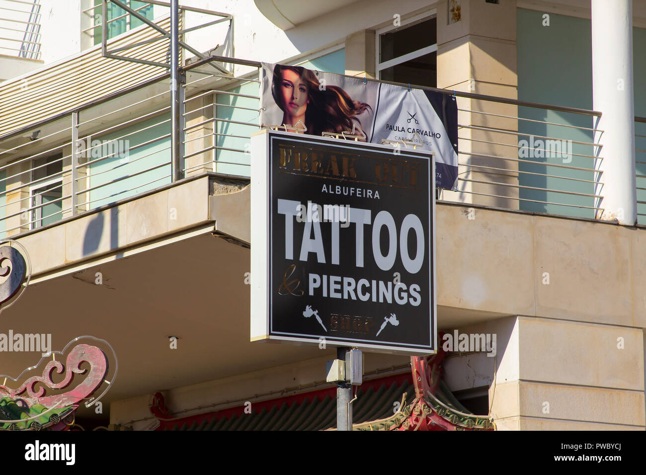 1 October 2018 Shop display sign for a Tatoo Salon and canvas poster advertising a hairdressers salon. Located on The Strip in Albuferia Portugal. - Stock Image