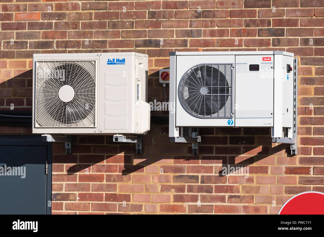 Pair of small commercial air condensing refrigeration units for shop air conditioning mounted on an outside wall in the UK. - Stock Image