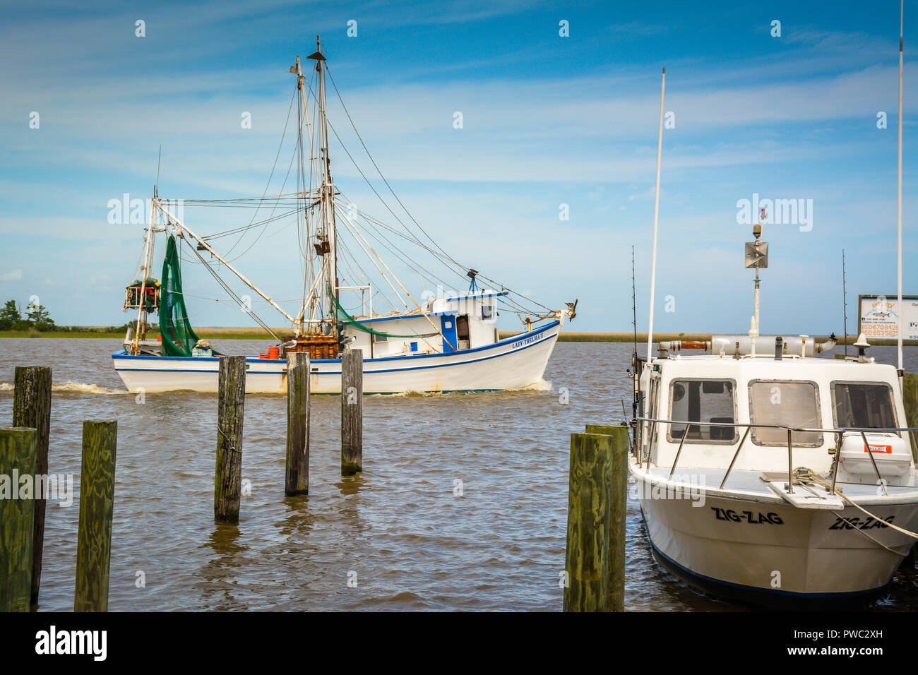 Fishing and tourist boats anchor and moor around the marina and docks in Apalachicola, FL on the bay in the Florida Panhandle Stock Photo