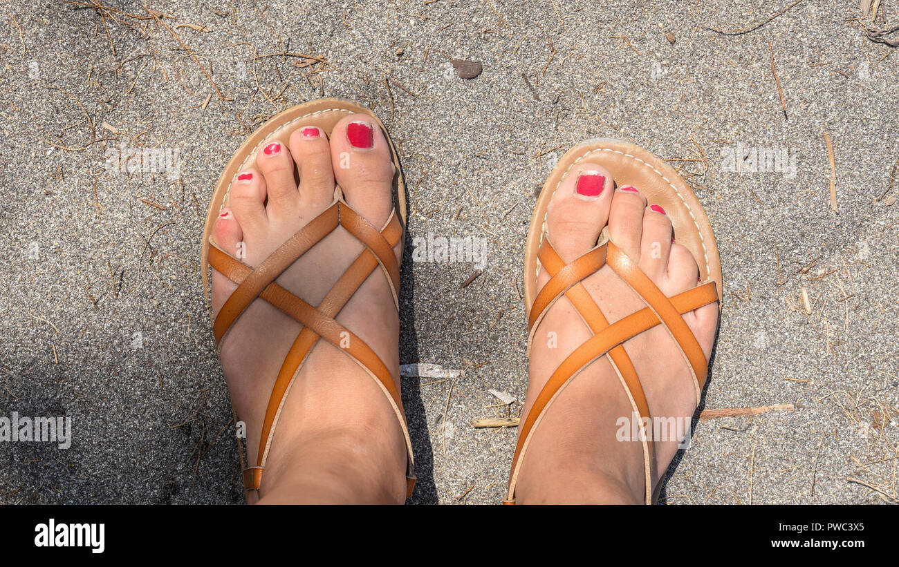 95473f0de0df Chipped nail polish on toes in sandals on the beach - Stock Image