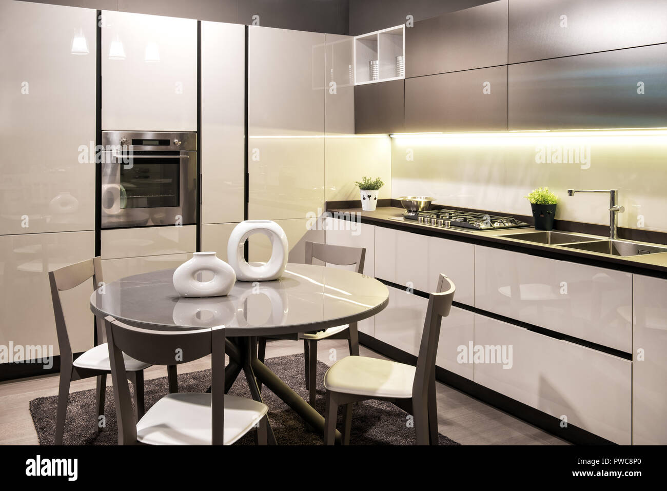 Modern built in kitchen with black and white decor and fitted appliances with circular dining table and chairs set with modern sculptural ceramics - Stock Image