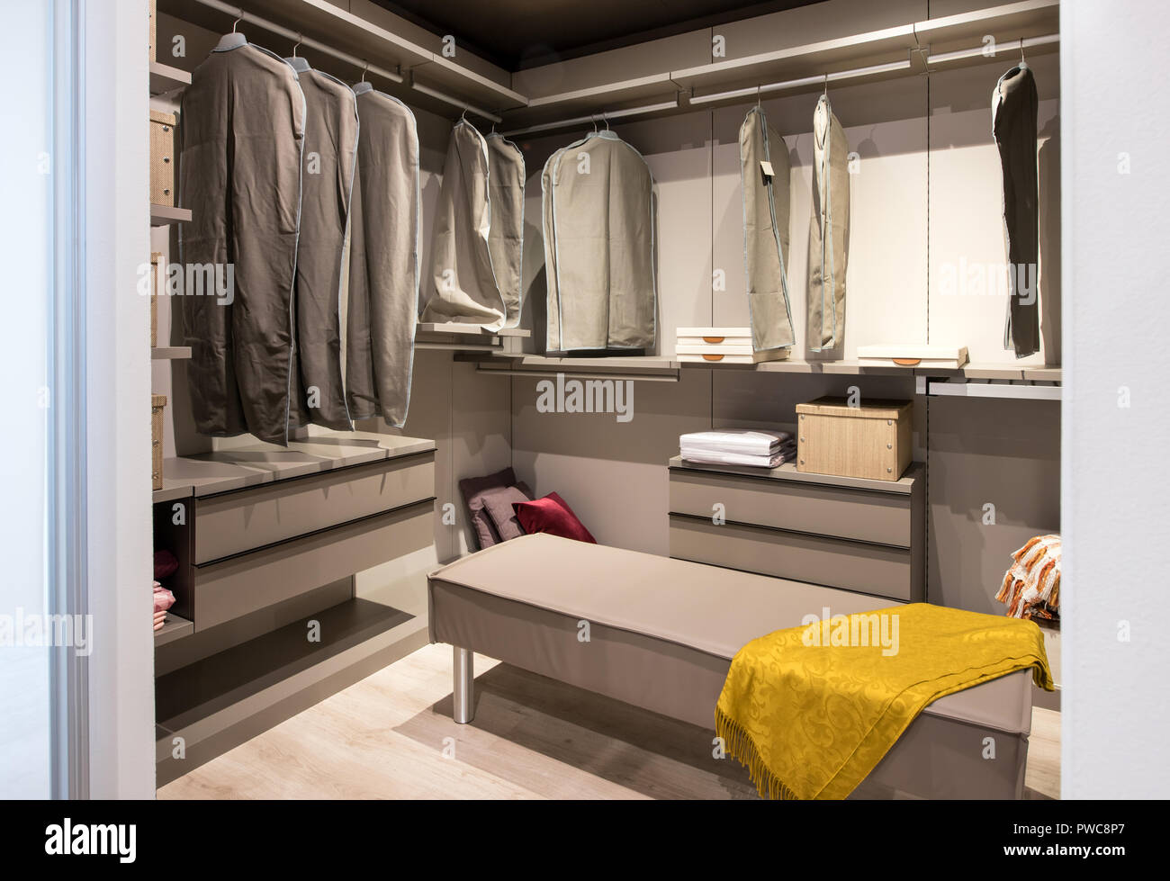 Interior of a walk in closet with hanging clothes and built in drawer units and seating in a luxury modern home - Stock Image