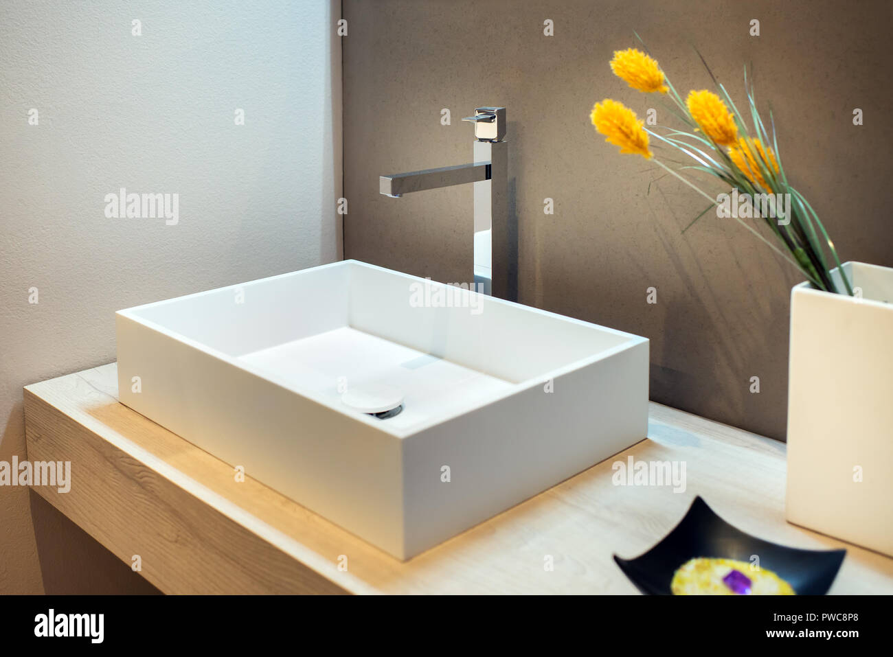 Stylish rectangular hand basin in modern bathroom with chrome faucet and flower arrangement - Stock Image