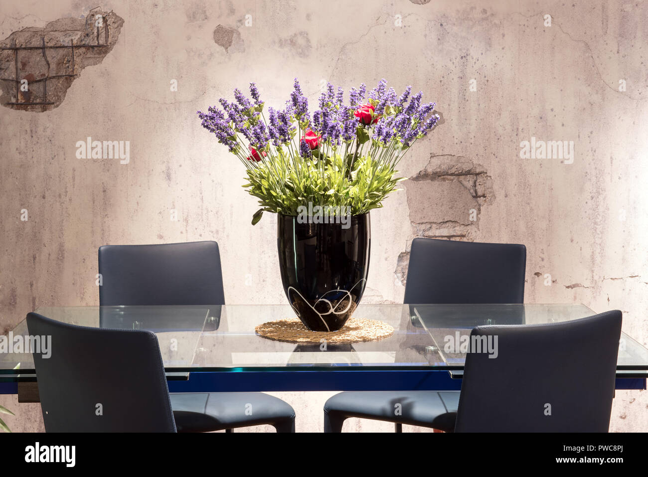 Dining Table With Floral Centerpiece With Colorful Blue And Red Flowers In A Vase And A Textured Grey Background Wall Stock Photo Alamy