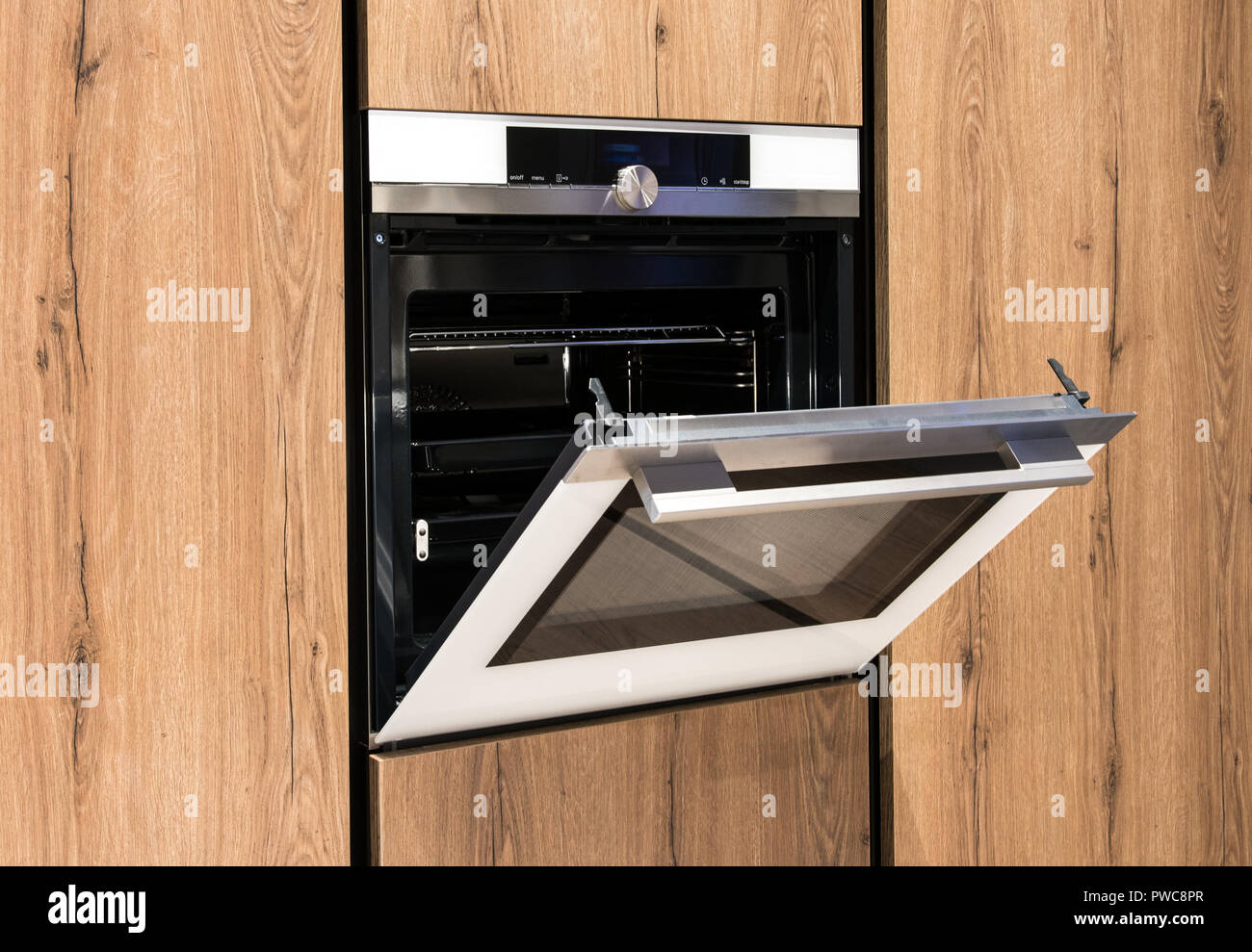 Built in oven in wooden fitted kitchen cabinets with the door open revealing the empty interior in a close up view - Stock Image