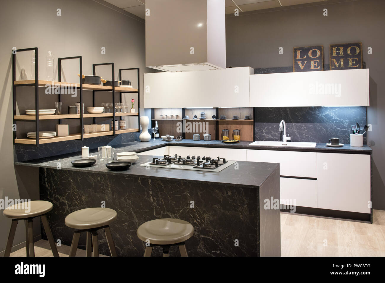Modern kitchen interior with centre island with bar stools and hob, white cabinets and open shelving - Stock Image