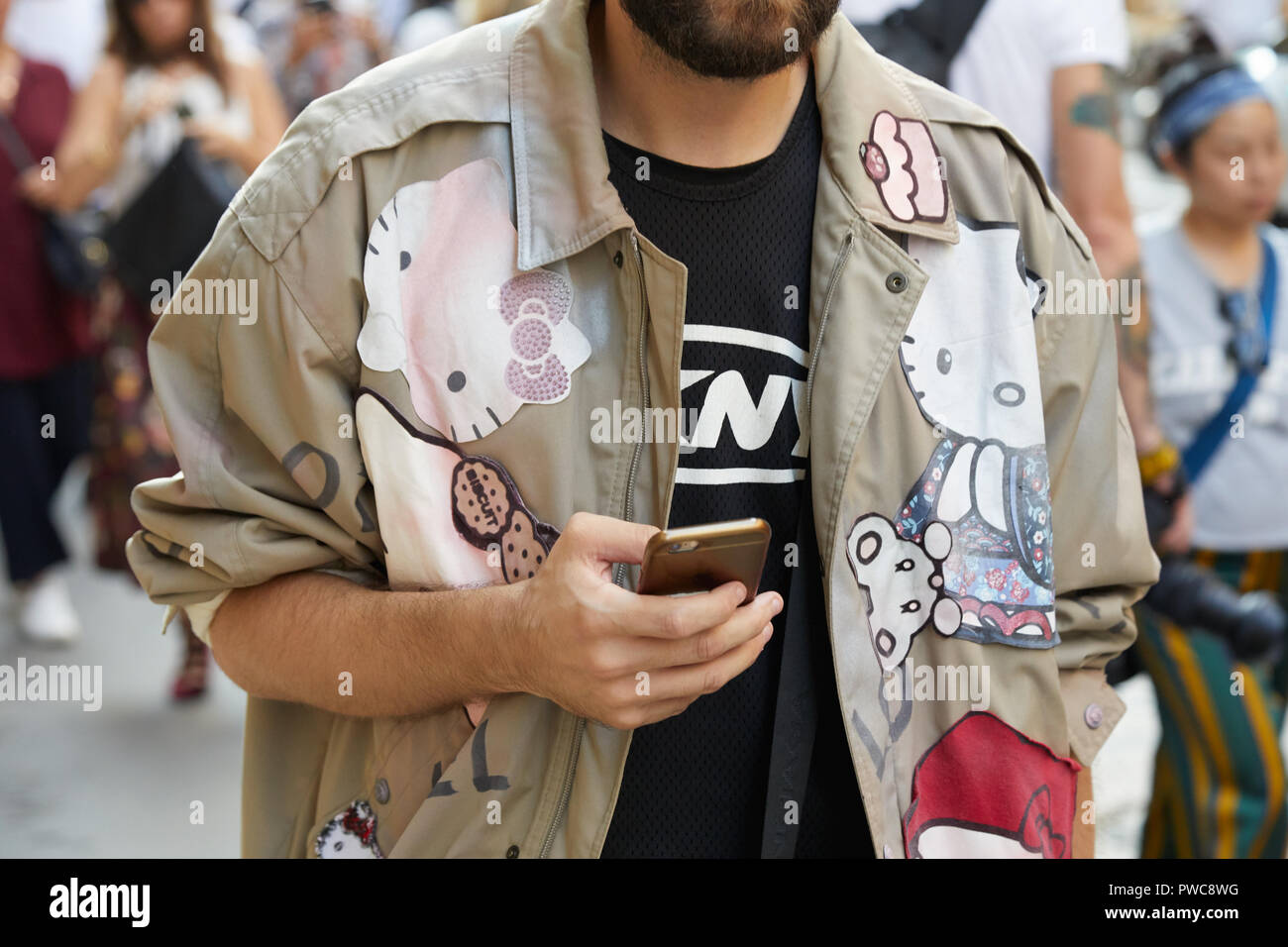 8a19d03db MILAN, ITALY - SEPTEMBER 20, 2018: Man with beige jacket with Hello Kitty  design before Vivetta fashion show, Milan Fashion Week street style
