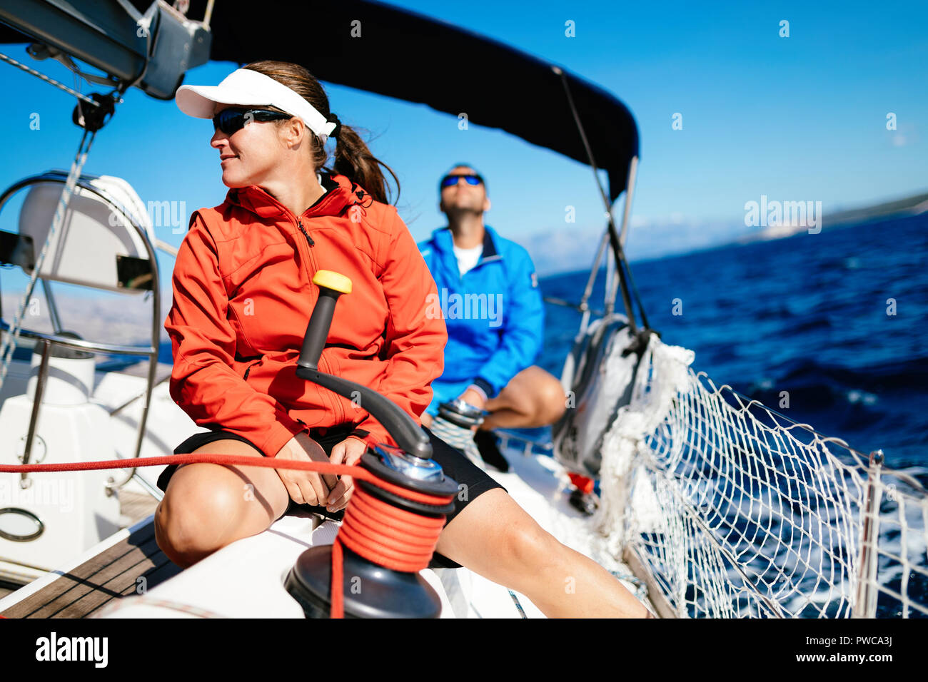 Attractive strong woman sailing with her boat - Stock Image