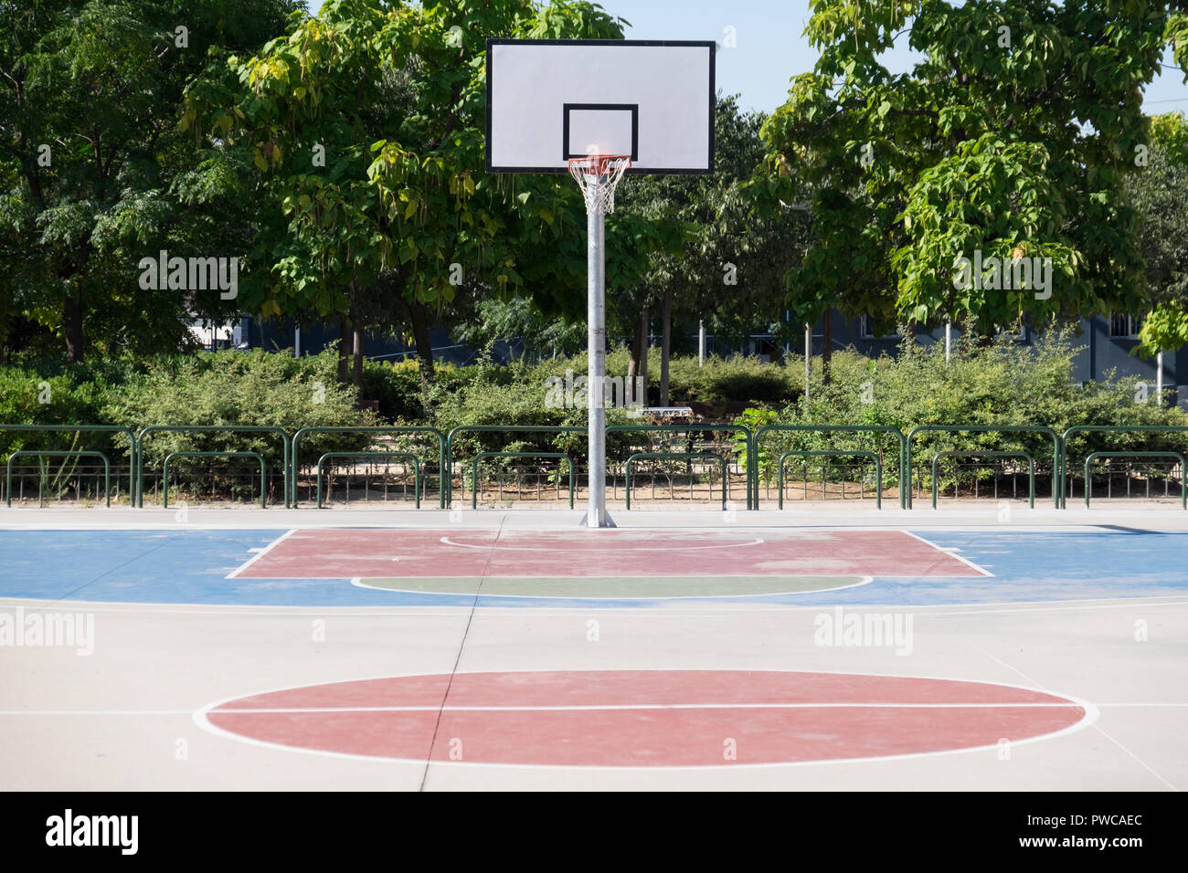 Basketball court in a park during midday in the summer with nobody. - Stock Image