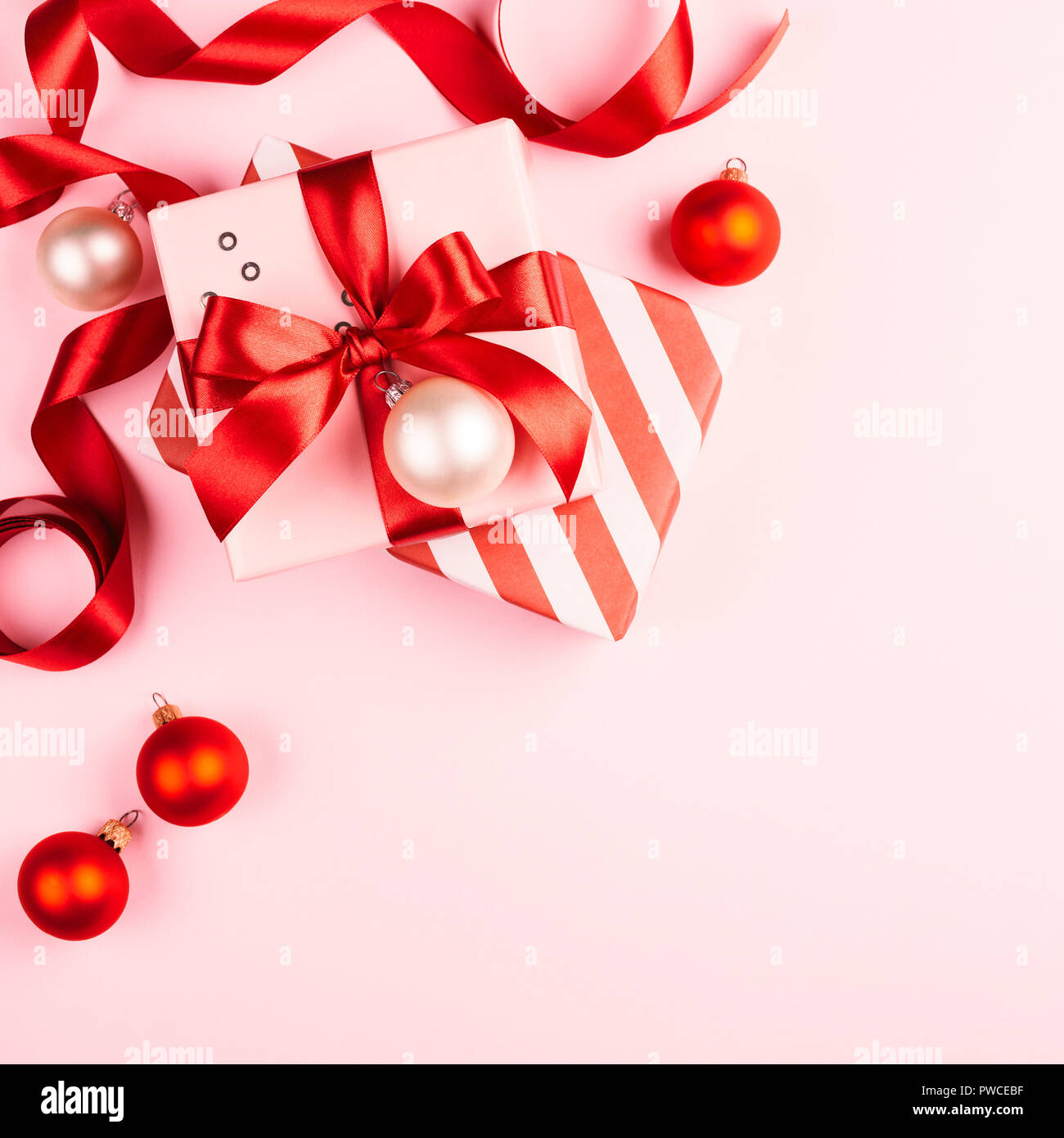 christmas gifts with red ribbon on pink background with decorations beautiful composition with gift boxes holiday background with copy space