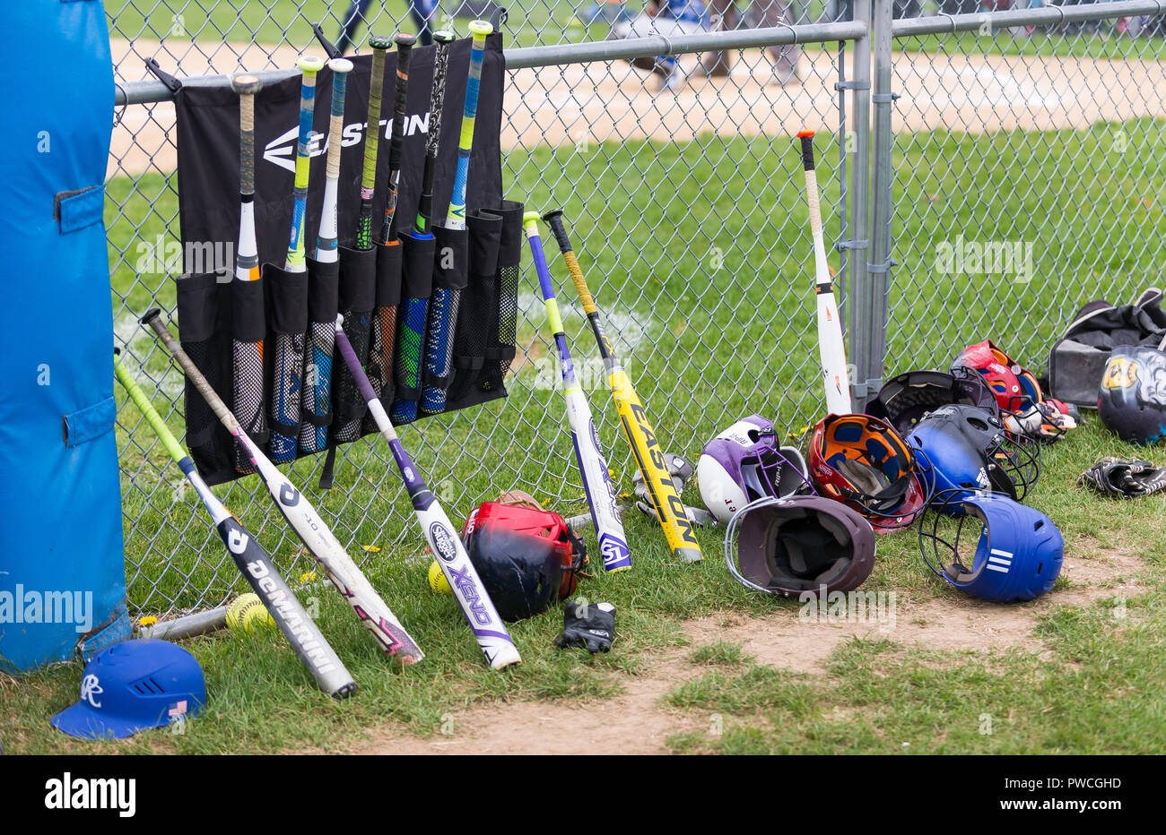 Softball equipment, ball, bats, helmets, scattered on ground and leaning on fence near dugout. - Stock Image