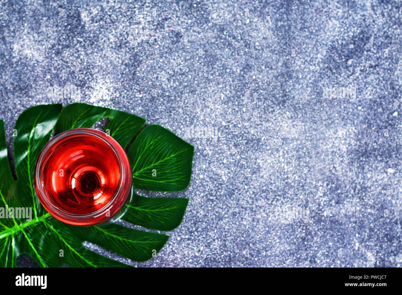 Wine in a wineglass and a tropical leaf. Top view. Wine drink on a gray background. Copy space Stock Photo