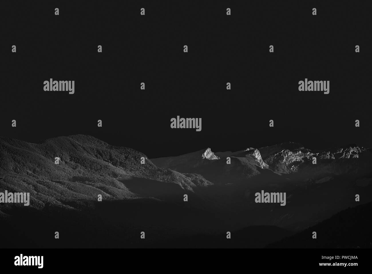 Lunigiana hills, north Tuscany, Italy. Beautiful evening landscape in monochrome black and white. Look other worldly, lunar landscape or similar, with horizon. - Stock Image