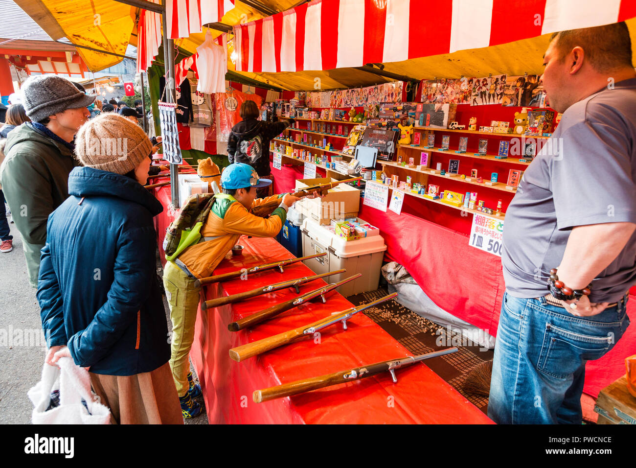 Japanese children's shooting gallery at stall during festival. Boy learning over counter holding rifle in both hands taking aim at target. - Stock Image