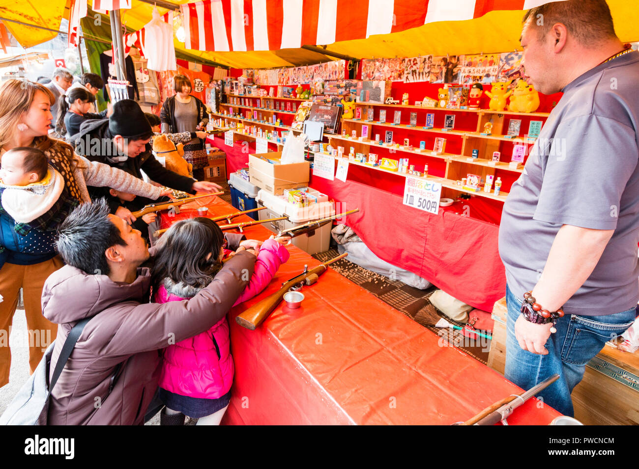 Japanese children's shooting gallery at stall during festival. Father kneeling down and helping his young daughter to hold rifle and aiming at target. - Stock Image