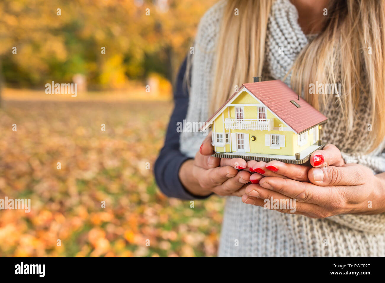 Young loving couple holding small model house in autumn garden or park Stock Photo