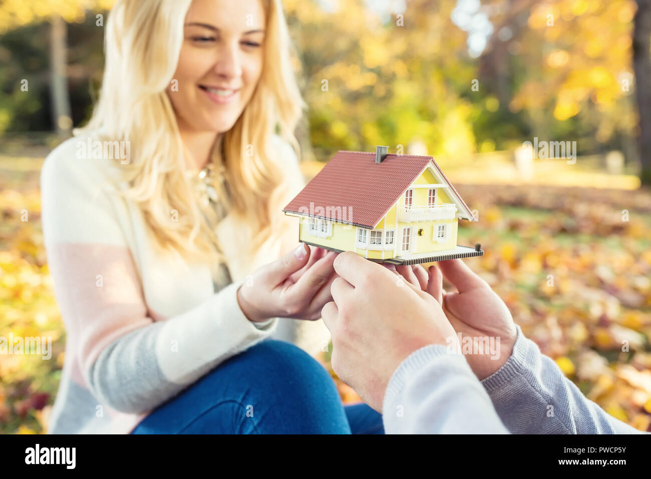 Young loving couple holding small model house in autumn garden or park. Stock Photo