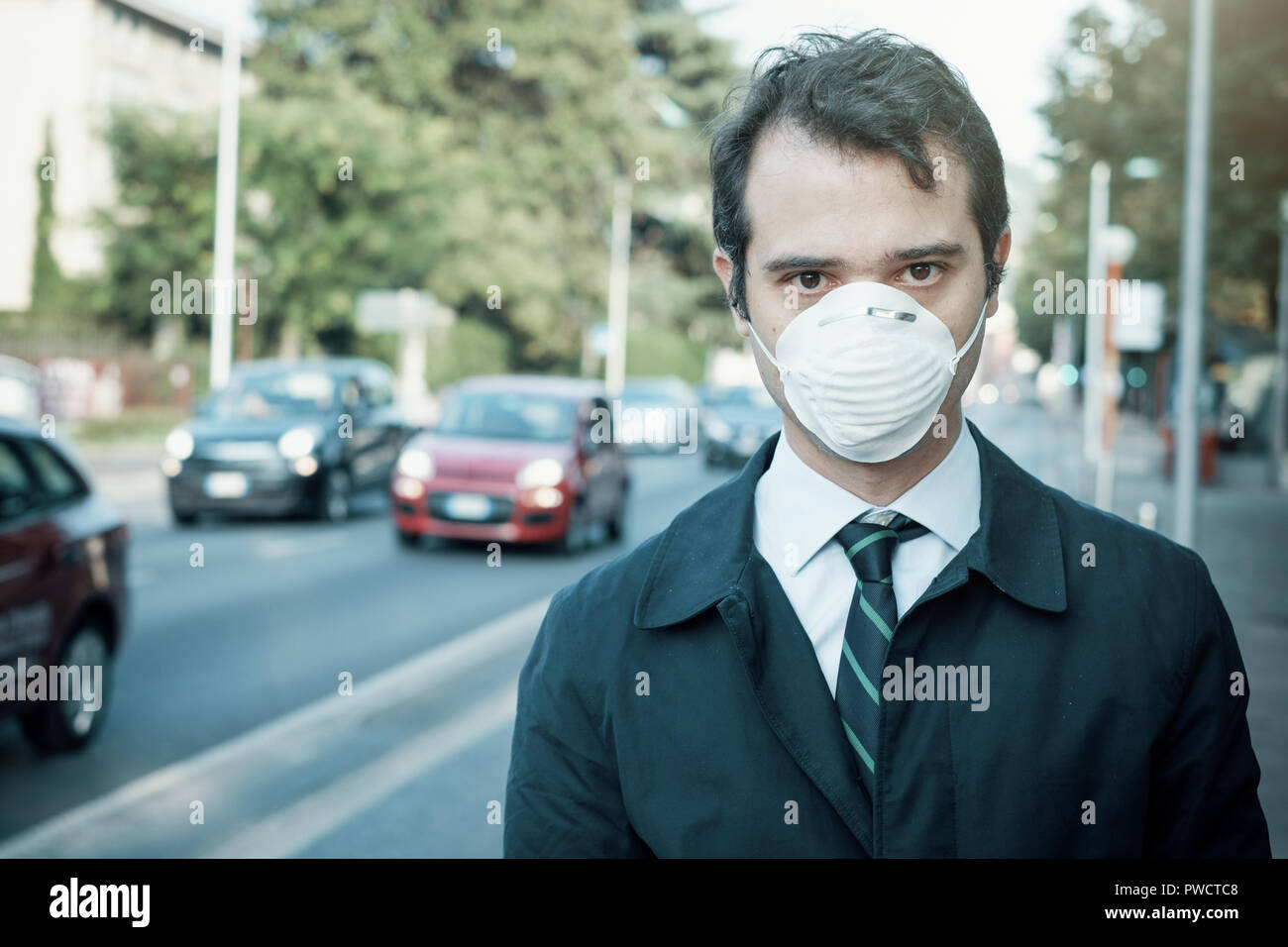 Man wearing mask against smog air pollution - Stock Image