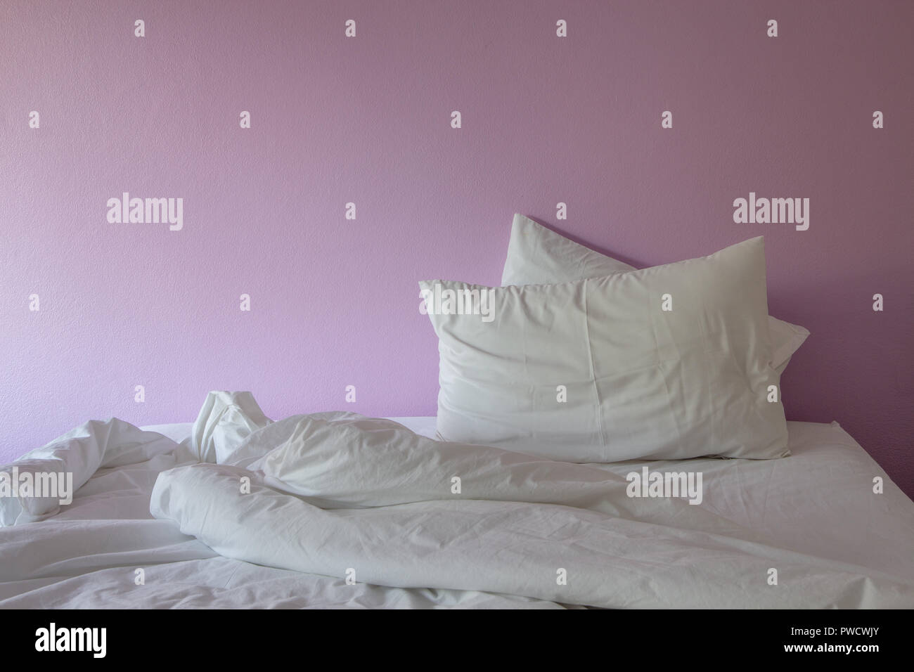 white wrinkle messy blanket and pillow on pink background. - Stock Image