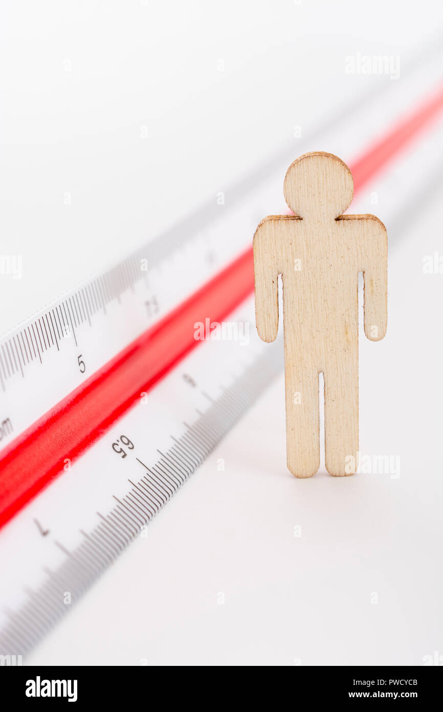 Macro small laser-cut wooden figure and ruler. Metaphor measuring personal performance, demographics concept, productivity, get the measure of a man. Stock Photo