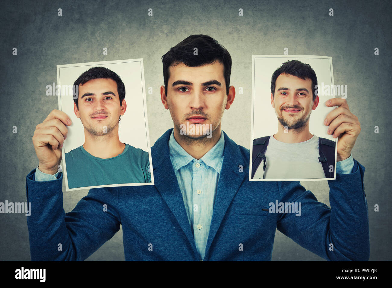 Young man holding two portrait photo sheets with different character. Change your personality, fake mask to hide the real expression of yourself. - Stock Image