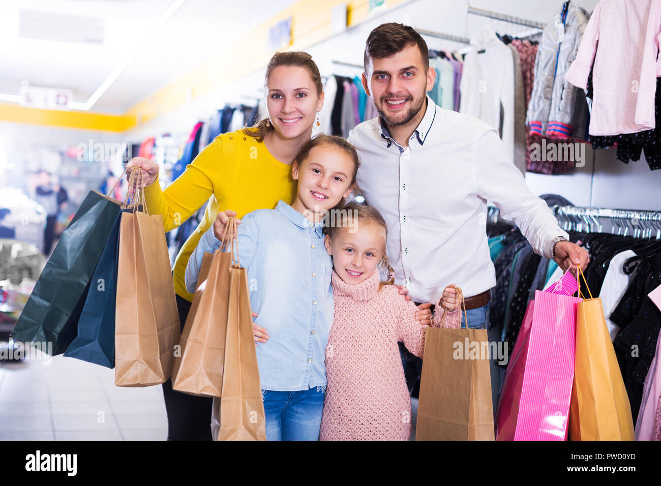 9ef62a0cb Portrait of happy family of four with shopping bags in clothing shop ...
