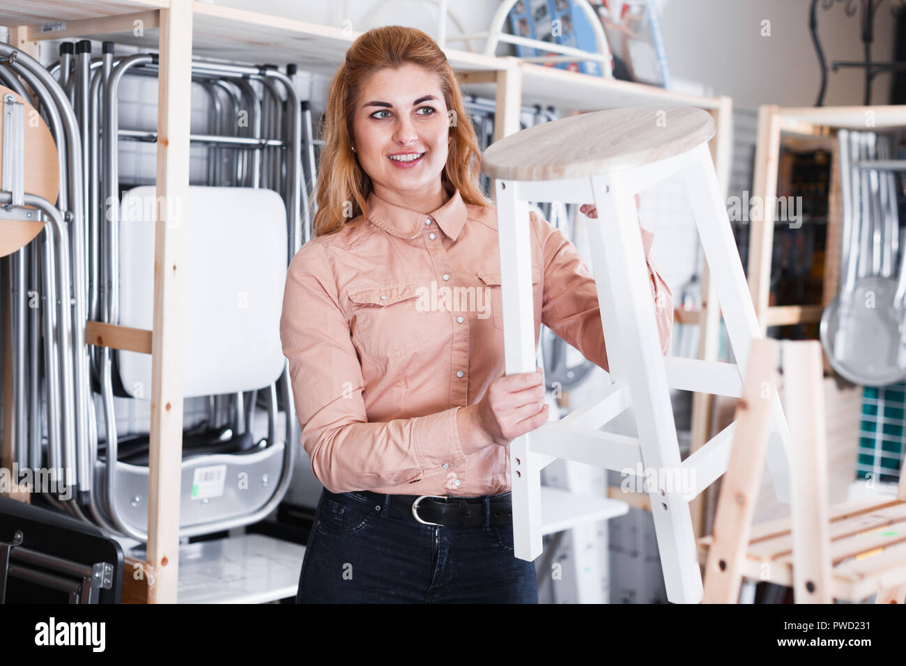 Young woman choosing comfortable backless stool in home furnishings store - Stock Image
