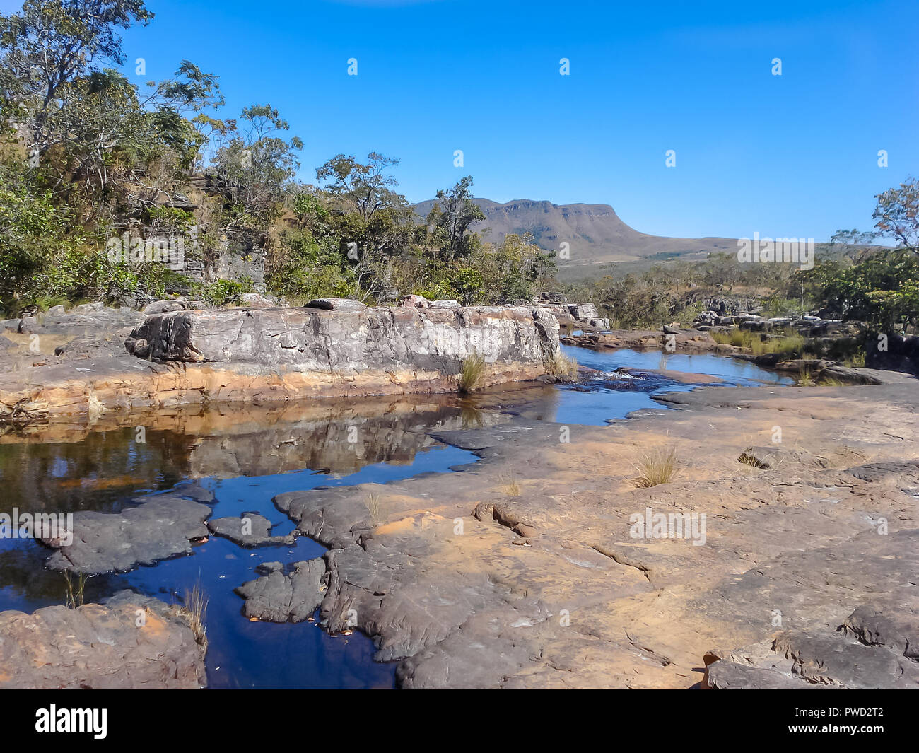 A relax view at the eye level of a stream running through the rocks in the foreground and mountains far away in the background - Stock Image